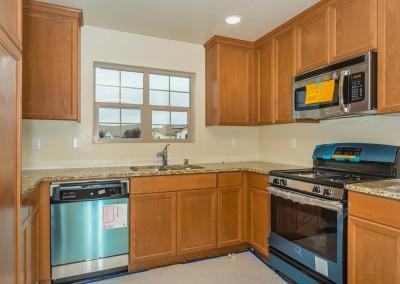Kitchen of the Monterey plan with upgraded counters and upgraded stainless steel appliances